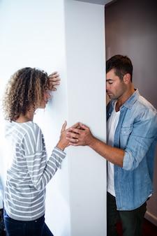 Расстроенная пара стоит на противоположных сторонах стены