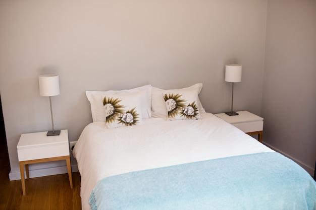 白いベッドシートと空のベッド