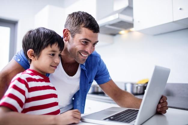 父と息子が台所でラップトップを使用して