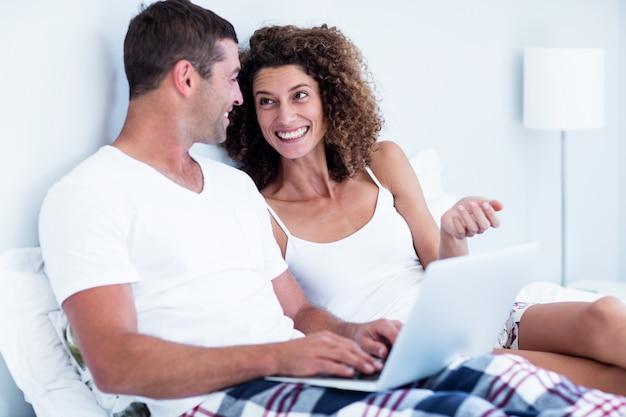 ベッドの上のラップトップを使用して幸せなカップル