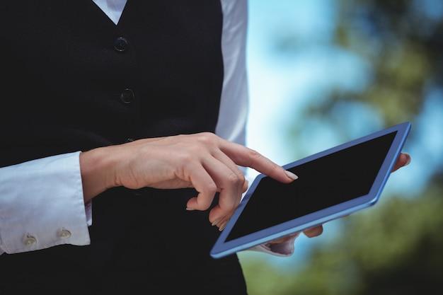 Улыбающаяся официантка, принимающая заказ с планшета