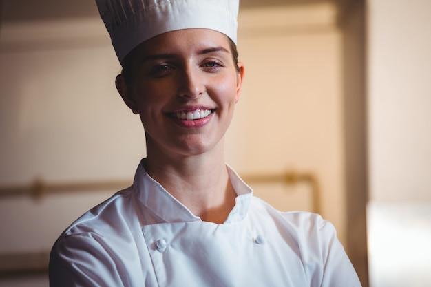 Шеф-повар улыбается и позирует со скрещенными руками