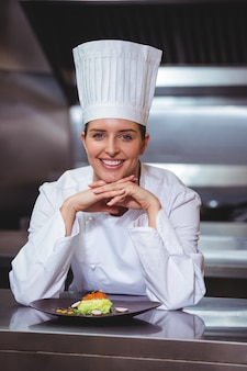 Шеф-повар опирается на прилавок с блюдом