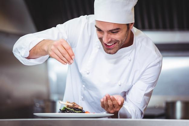 Шеф-повар посыпать специями на блюдо
