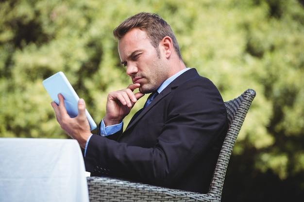 Вдумчивый бизнесмен с помощью планшета