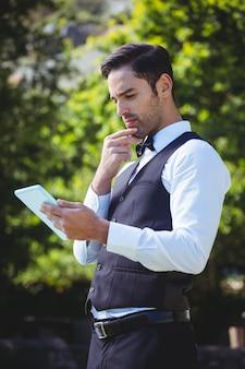 Красивый официант с помощью планшетного компьютера