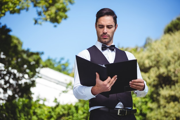 Красивый официант смотрит на меню
