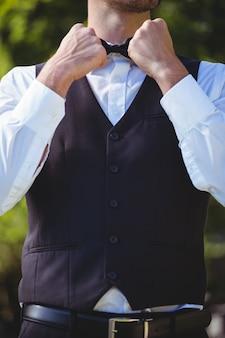 Красивый официант, прикрепляющий галстук-бабочку