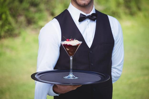 Красивый официант держит поднос с пустыней