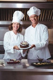 彼らが作ったケーキを提示するシェフ