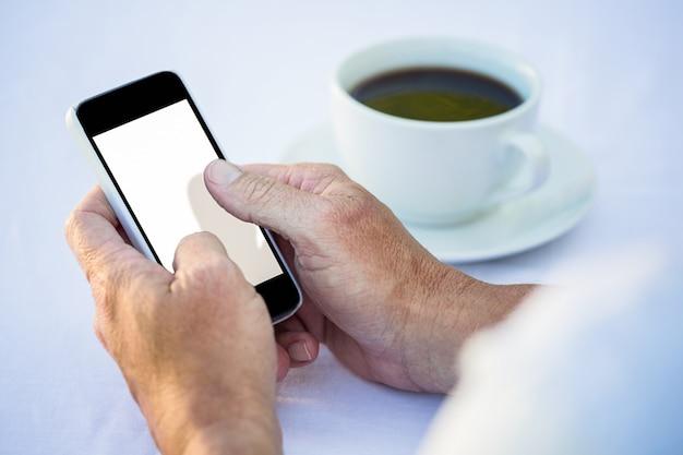 スマートフォンを使用して、コーヒーを飲んでいるカジュアルなビジネスマン