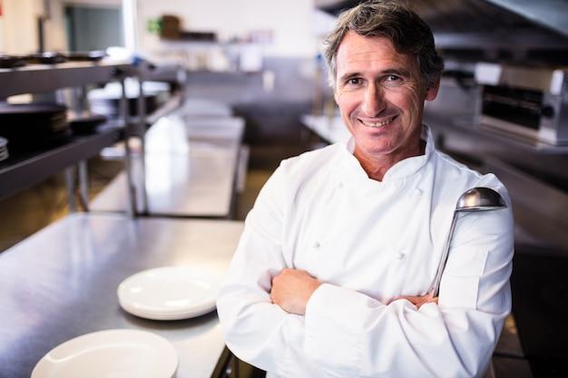 Улыбающийся шеф-повар держит ковш на кухне