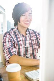 オフィスのコンピューターを使用して笑顔の流行に敏感なビジネスマン