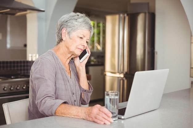 Серьезная старшая женщина разговаривает по мобильному телефону