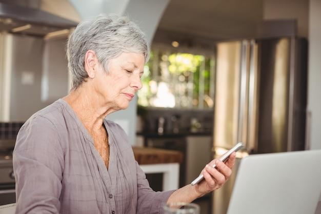 Старший женщина, держащая мобильный телефон