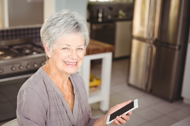 携帯電話を保持している幸せな年配の女性の肖像画