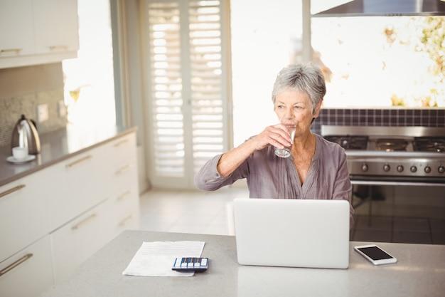 年配の女性が台所のテーブルに座って水を飲む