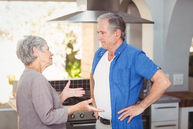 Пожилая пара спорит на кухне