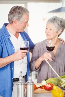 ワイングラスを持つロマンチックな年配のカップル