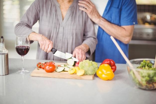 Веселая пара старших готовит салат