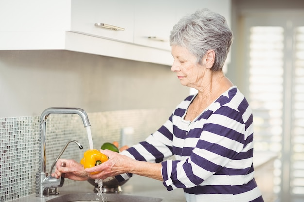 Пожилая женщина моет сладкий перец
