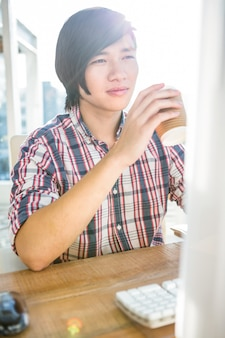 流行に敏感なビジネスマンのオフィスでコンピューターを使用しながらコーヒーを飲む
