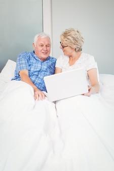 ベッドの上のラップトップで年配のカップル