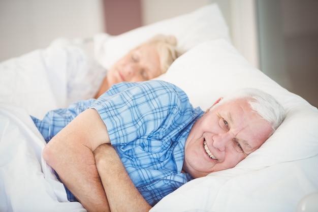 彼の妻とベッドに横たわっている男の肖像
