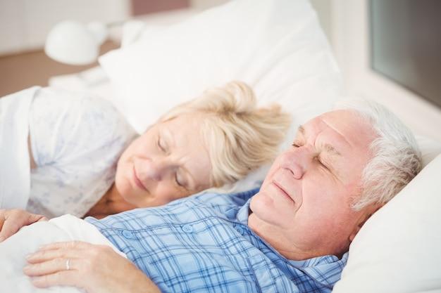 Пожилая пара спит на кровати у себя дома