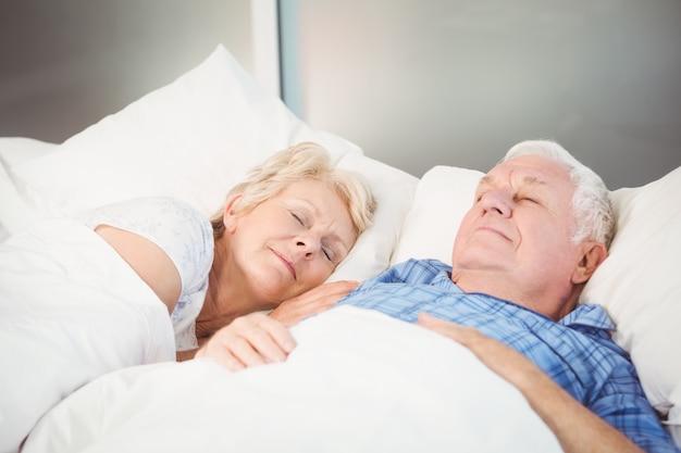 自宅のベッドで寝ている年配のカップル