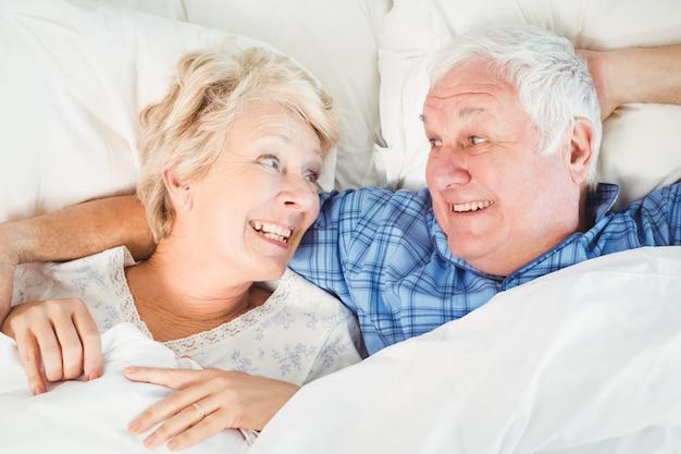 ベッドに横になっている幸せな先輩カップル