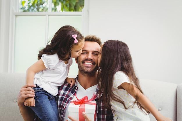 Отец держит подарочную коробку и его дочери целуют его