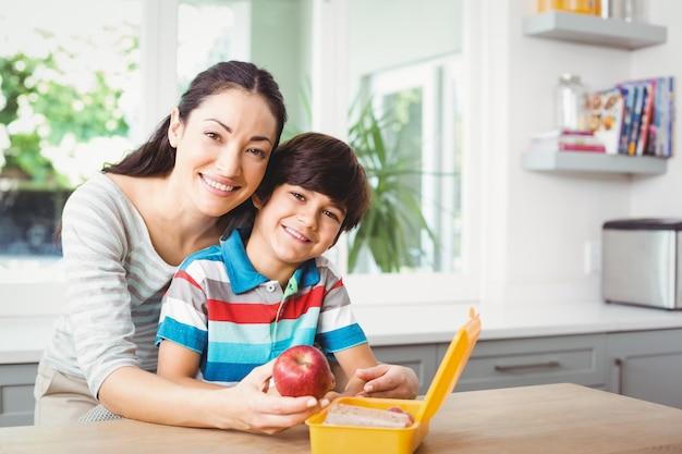 母と息子のランチボックスに笑みを浮かべてください。