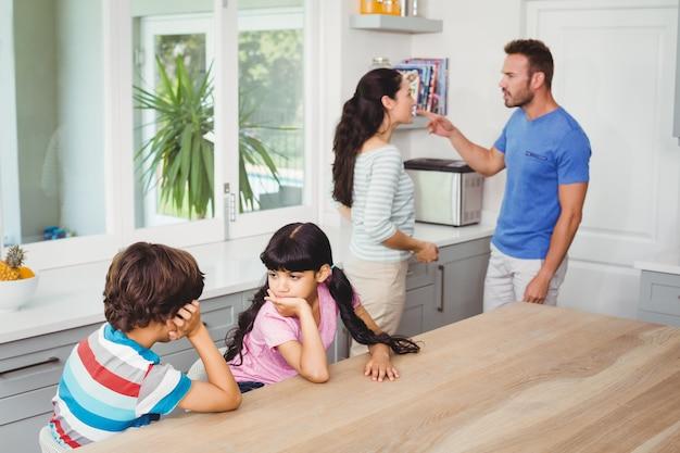 けんかばかりしている両親とテーブルに座っている子供たち