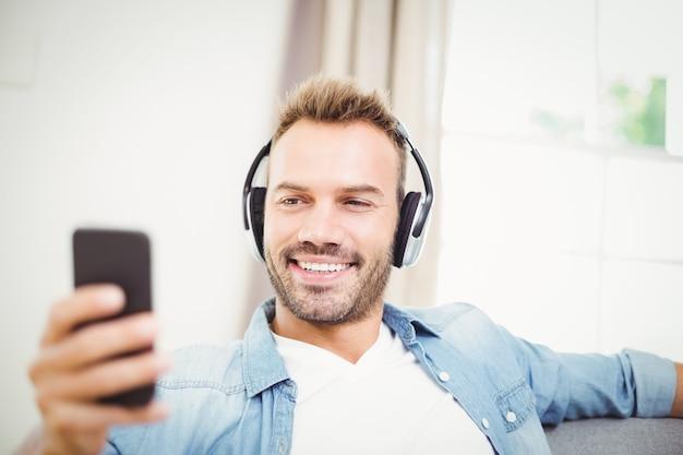 音楽を聴きながら携帯電話を使用して幸せな男