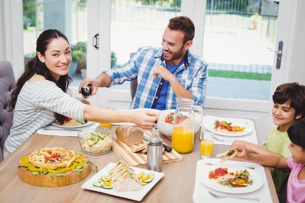 ダイニングテーブルに座って食べ物を持っている幸せな家族