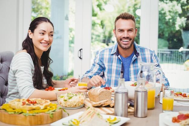 ダイニングテーブルに座って笑顔のカップル