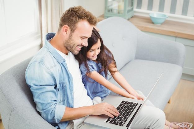 Улыбаясь, отец и дочь, используя ноутбук, сидя на диване