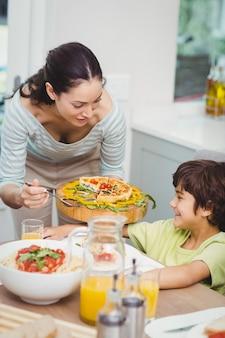 息子に食べ物を提供する母