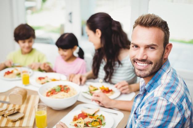 ダイニングテーブルで家族と一緒に笑顔の父の肖像