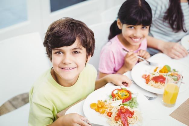 Улыбающиеся дети, имеющие еду