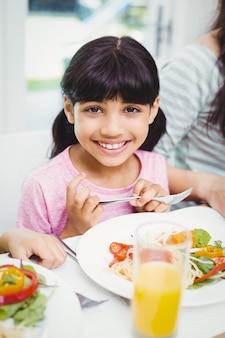 Улыбающаяся девушка сидит за обеденным столом