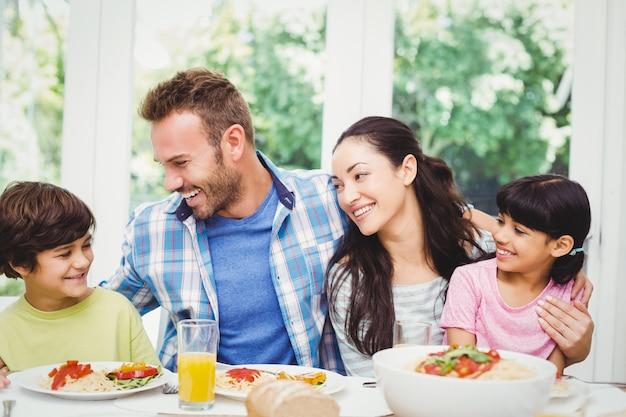 ダイニングテーブルに座って笑顔の家族