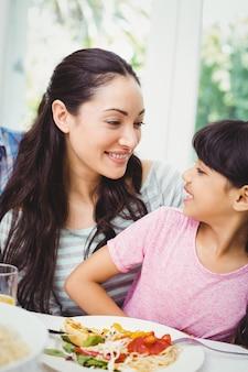 Счастливая мать и дочь сидят за обеденным столом