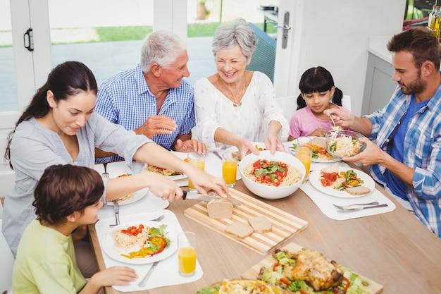 食べ物を持って笑顔の多世代家族