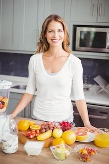 キッチンで果物と笑顔の女性