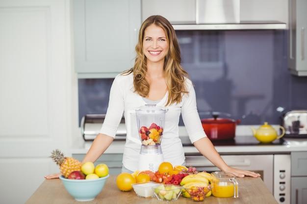 果物とテーブルに立っている陽気な女性