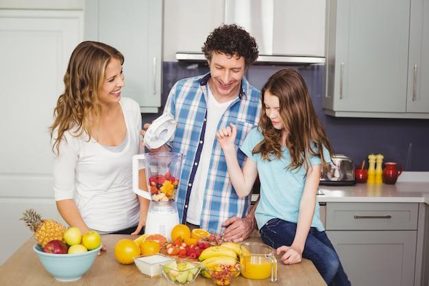 笑顔の家族がフルーツジュースを準備します。