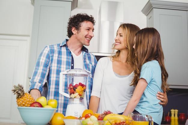 幸せな家族がテーブルでフルーツジュースを準備します。