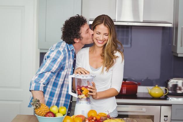 Мужчина целует женщину готовит фруктовый сок